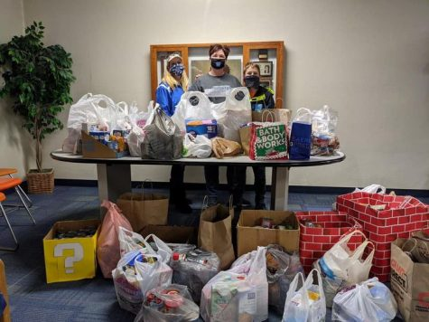Mrs. Boyce, Mrs. Hanley and JD Hanley showcase the food collected at the drive-by food drive.