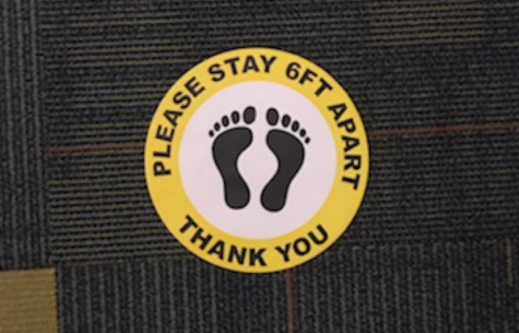 A sticker reminds students to stay socially distant.